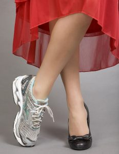 woman with crossed legs wearing dress shoes on one foot and runners on the other